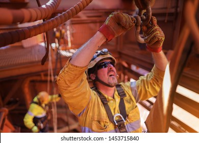 Industry rope access rigger abseiler high risk worker wearing fall safety body abseiling harness working at height performing fastening D shackle pin into other D shackle lifting lug prior to used