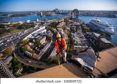 Industry rope access worker using twin ropes wearing a helmet, working at height in fall arrest position abseiling down at construction building site background is Sydney harbour bridge, Australia