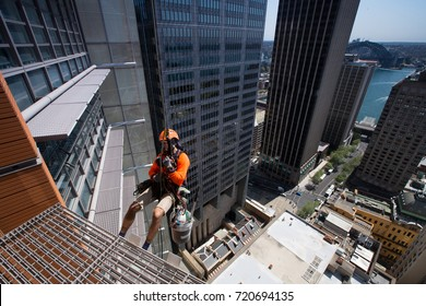 Industry rope access worker wearing fully safety equipment hardhat completed his cleaning windows and abseiling from high rise building site in city of Sydney city CBD, Australia.