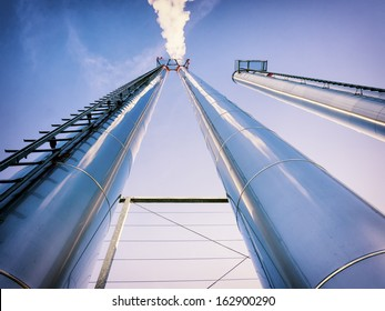 industry smoke stacks in front of blue sky