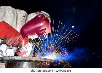 industry welding worker with a metal piping in factory with spark light by Mig wear equipment protective PPE for safety concept on black background