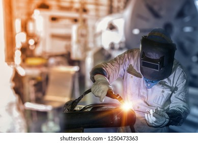 Industry worker at the factory welding metal steel pipe by TIG weld torch gas argon  on Dark tone