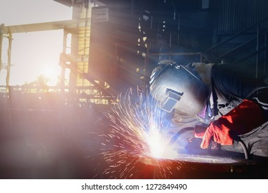 Industry worker at the factory welding steel pipe by Mig with sparks light weld wearing PPE equipment protective on on dark tone