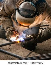 Industry worker welding iron pieces at work