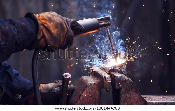 Industriearbeiter, die Eisenschweißteile bei der Arbeit schweißen