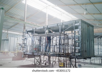 Industry worker with welding steel to build container structure.