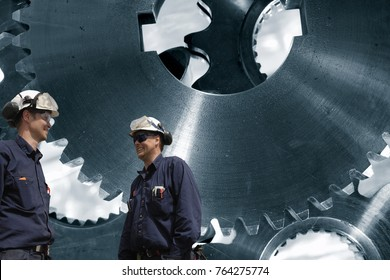 industry workers in front of large gears and cogs machinery, steel industrial
