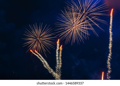 Inexpensive fireworks over blue sky, yellow and white with colour sparks. Selective focus. Bright and shiny. Celebration concept.