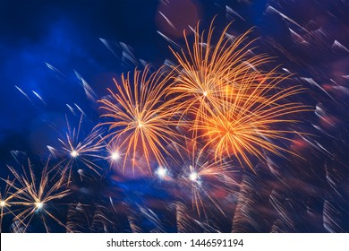 Inexpensive fireworks over blue sky, red, green, blue and white with colour sparks. Selective focus. Bright and shiny. Celebration concept.