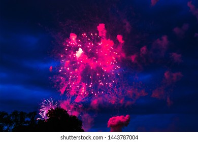 Inexpensive fireworks over the city red, pink and white. Bright and shiny.  For any purpose. Celebration concept.