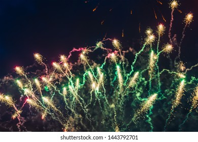 Inexpensive fireworks over the city red, green and yellow on the blue sky. Bright and shiny.  For any purpose. Celebration concept.