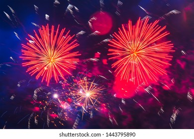 Inexpensive fireworks over the city red, and yellow with colour smoke and sparks on the blue sky. Bright and shiny.  For any purpose. Celebration concept.