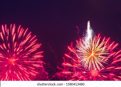 Inexpensive fireworks, over the city, red and pink. Motion blur. Light flares. For any purpose