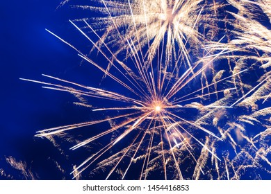 Inexpensive fireworks over the city yellow, blue and white. Bright and shiny.  For any purpose. Celebration concept.