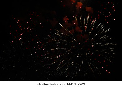 Inexpensive fireworks, over dark city sky, red and yellow. For any purpose. Celebration concept.