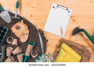 Inexpensive organic food production and gardening equipment, top view of tools and seed on wooden table in garden with some euro coins as concept of low cost investment in agricultural activity