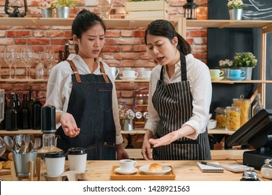 Inexperienced girl barista. angry owner of restaurant scolding new employee behind bar counter. manager dissatisfied with waitress's work of making coffee and baking croissant in modern cafe shop.
