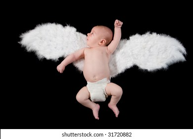 Infant with angel wings on black background.