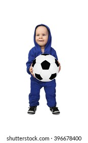 Infant baby in blue suit stands with big soccer ball in hands isolated on white background