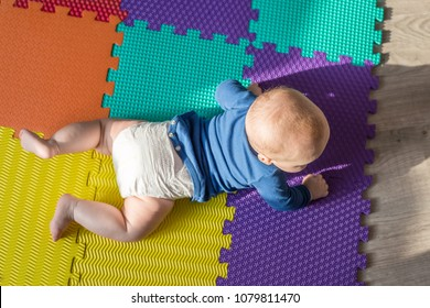 Infant baby boy playing on colorful soft mat. Little child  making first crawling steps on floor. Top view from above