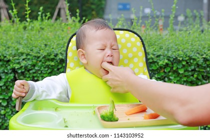 Infant baby boy sitting on kid chair eating with something stuck in his mouth and mother help to keep out.