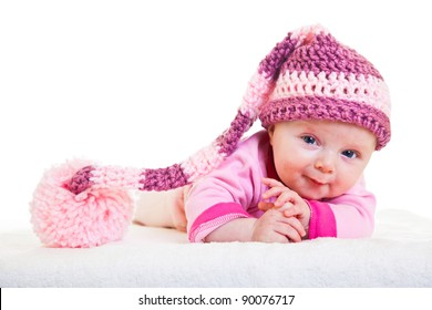 Infant baby girl raising head in funny hat isolated on white