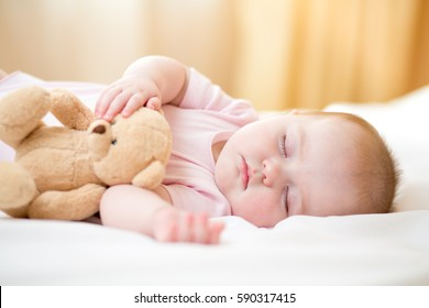 infant baby girl sleeping with plush toy