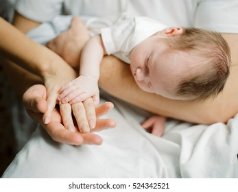 infant baby in mother's and father's hands