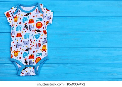 23fc09ed8d6 Infant baby printed romper and copy space. Cute cotton newborn wear on blue  wooden background