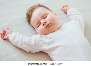 Infant baby sleeping on white sheets