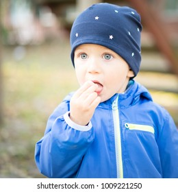infant boy with cap at the park puts his fingers in his mouth with a perplexed face, amazed and looks into space.