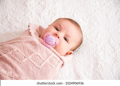 Infant care, beauty of childhood concept. Little newborn baby has teat in mouth when lying down on bed inside wrap