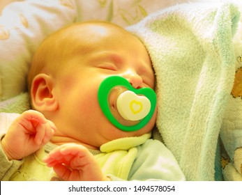Infant care, beauty of childhood concept. Little newborn baby sleeping calmly in bed with teat in mouth.