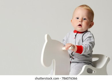 Infant child baby boy kid toddler sitting ride white little wooden horse toy in red stripes body cloth looking at the corner on gray background