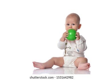 Infant child baby boy toddler in diaper and white shirt is sitting  with green ball toy in his hands, biting it isolated on white background with free copy space