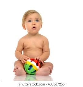 Infant child baby boy toddler playing holding green red yellow ball in hands on a floor on and looking at the corner isolated a white background