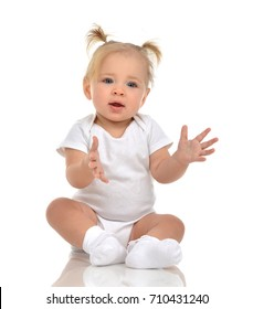 Infant child baby boy toddler holding imaginary object in hands fingers up on a floor on and looking on it isolated a white background