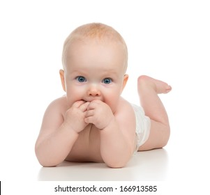 Infant child baby girl in diaper lying happy smiling and eating hands on a white background