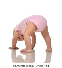 Infant child baby girl in diaper standing upside down on head in pink cloth looking up isolated on a white background