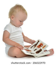 Infant child baby girl toddler sitting and reading book on a white background
