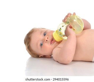 Infant child baby kid lying and drinking water from the feeding bottle on a white background