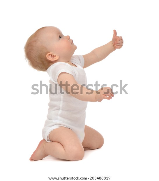 Infant child baby toddler happy looking up smiling with hand thumb up sign isolated on a white background