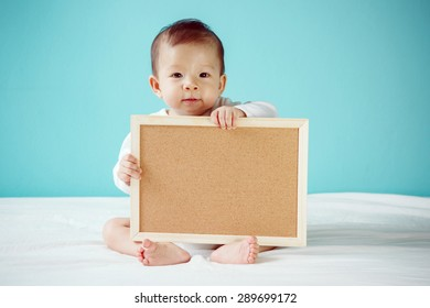 Infant child holding empty board with copy space for your text, Baby healthy and family concept