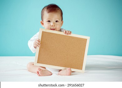 Infant child holding empty board copy space, new family and love concept.