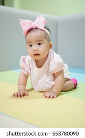 Infant Girl Portrait, Happy baby learn to craw around and stand, with trendy headband with a bow