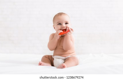 Infant growing first tooth. Cute newborn baby biting teether in bed, copy space