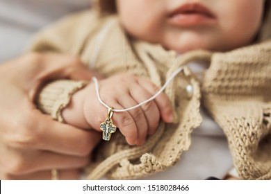 Infant is holding cross white christening in orthodox church