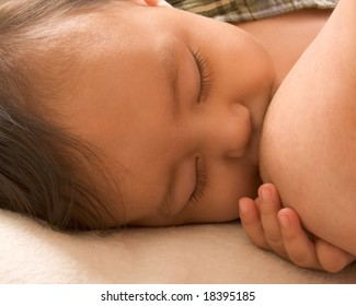 Infant holding his mother breast while she is nursing him