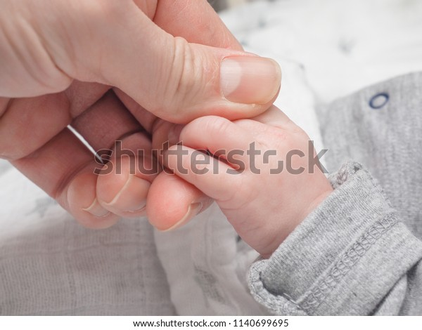 Infant holding onto finger of adult male at closeup