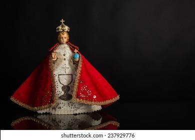 Infant Jesus of Prague in red vestments on a dark background